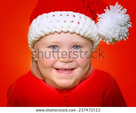 Closeup portrait of cute little baby girl wearing Santa hat isolated on red background, funny festive costume for Christmas celebration - stock photo