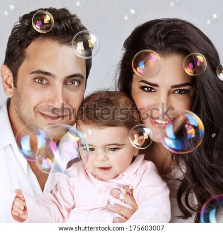 Closeup portrait of cute little baby girl with lovely parents enjoying soap bubbles, playing with bubbles water, happy childhood concept - stock photo