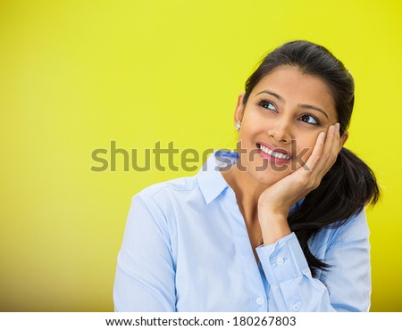 Closeup portrait of cute pretty smiling young woman student thinking hand on cheek looking up having idea, isolated on green, yellow background. Positive emotion facial expressions, feelings, attitude - stock photo