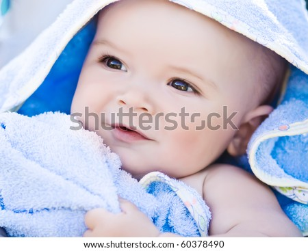 Closeup portrait of cute smiling baby boy in blue towel - stock photo