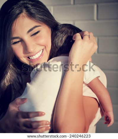 Closeup portrait of cute smiling mother holding on hands little baby, having fun at home, happy parenthood, family love concept - stock photo