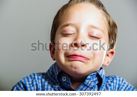 Closeup portrait of cute young boy looking sad crying - stock photo