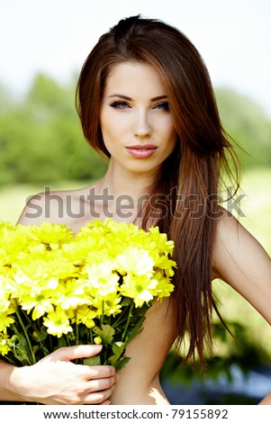 Closeup portrait of cute young girl with yellow flowers smiling outdoors - stock photo
