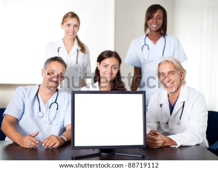 Closeup portrait of doctors and nurses in a meeting with a monitor in the foreground - stock photo