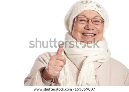 Closeup portrait of elderly woman at wintertime with thumb up, smiling. - stock photo