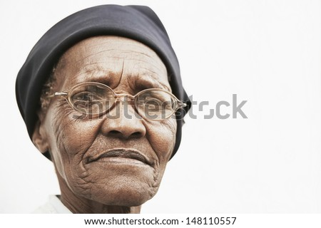 Closeup portrait of elderly woman wearing glasses over white background - stock photo