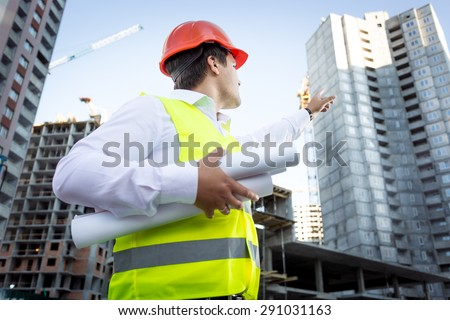 Closeup portrait of foreman with blueprints pointing hand at high building - stock photo