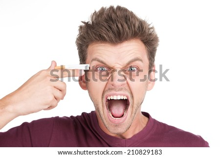 Closeup portrait of frustrated stressed young man. young man placing cigarette on head mimicking gun - stock photo