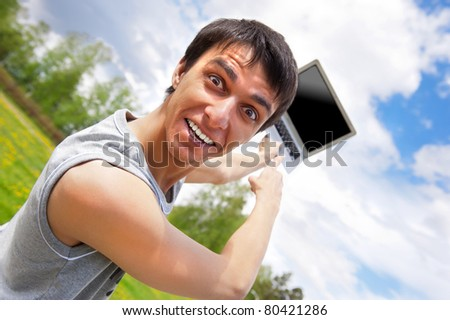 Closeup portrait of funky casual young man pointing at laptop screen outside at summer park - stock photo