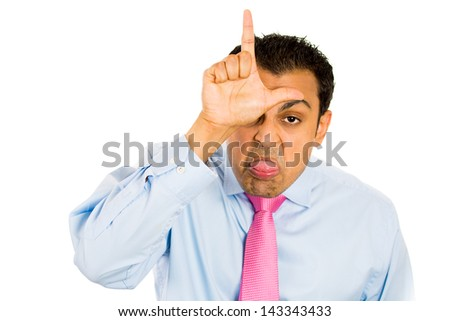 Closeup portrait of funny man displaying a loser sign on his forehead and sticking tongue out at you, isolated on a white background - stock photo
