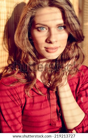 closeup portrait of gently looking at camera beautiful young blue eyes lady with shadow from window blinds - stock photo