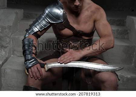 Closeup portrait of gladiator in armour sitting on steps of ancient temple looking at sword. Concept of masculine power, strength - stock photo