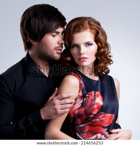 Closeup portrait of glamour young sexy couple in love posing at studio in elegance clothes. - stock photo