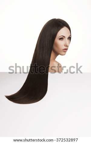 Closeup portrait of gorgeous brunette woman posing in studio. Beautiful Woman with Long Healthy and Shiny Smooth Hair. Hairstyle, haircare concept. - stock photo