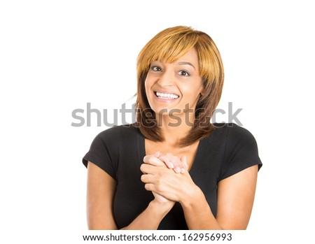 Closeup portrait of grateful happy young woman smiling with hands clasped close to chest, isolated on white background with copy space to left. Positive human emotion facial expressions - stock photo