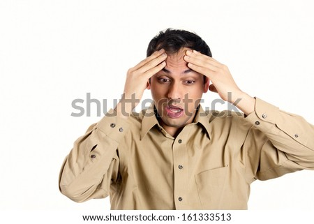 Closeup portrait of guy in brown shirt overwhelmed overcome pressured with work, hands on forehead, isolated on white background. Negative human emotion facial expressions. - stock photo