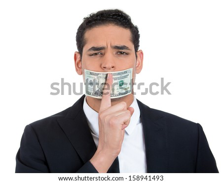 Closeup portrait of handsome corrupt guy in black suit with twenty dollar bill taped to mouth and showing shhh sign, isolated on white background. Bribery concept in politics, business, and diplomacy. - stock photo