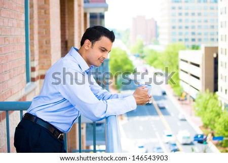 Closeup portrait of handsome guy enjoying his drink on an outside balcony, isolated on a city background with trees and buildings and cars and roads - stock photo