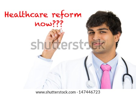 Closeup portrait of handsome male health care professional or doctor or nurse writing the words 'healthcare reform now?' , isolated on white background with copy space - stock photo