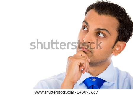 Closeup portrait of handsome man thinking deeply with hand on chin looking upwards, isolated on background with copy space to left - stock photo