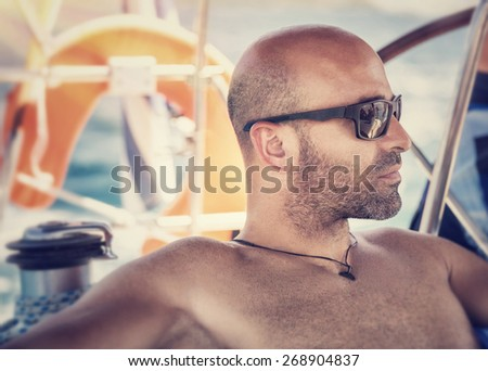 Closeup portrait of handsome shirtless man on sailboat, sexy sailor wearing sunglasses and enjoying sea trip, active lifestyle, summer travel and vacation concept - stock photo