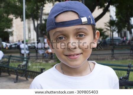Closeup portrait of handsome smiling young Caucasian boy with hat worn backwards in city park - stock photo