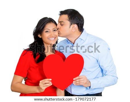 Closeup portrait of handsome young man happily giving red heart and kissing pretty beautiful woman, isolated on white background. Positive emotion facial expression feelings.Puppy love is in the air. - stock photo