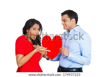 Closeup portrait of handsome young man happily giving red heart to pretty beautiful shocked woman, isolated on white background. Positive emotion facial expression feelings.Puppy love is in the air. - stock photo
