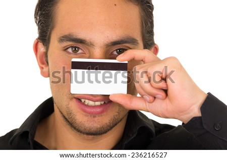closeup portrait of handsome young man holding credit card in front of his face isolated on white - stock photo