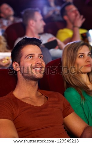 Closeup portrait of handsome young man sitting at movie theater, smiling. - stock photo