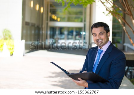 Closeup portrait of handsome young smiling businessman in suit reviewing some documents, standing outside of his company building, on a sunny day, isolated on a city urban background. Corporate life. - stock photo