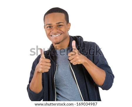 Closeup portrait of handsome young smiling man in black hoody giving two thumbs up at camera sign isolated on white background. Positive human emotions facial expression feelings. Symbols - stock photo