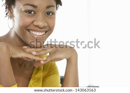 Closeup portrait of happy African American woman with hands on chin isolated on white background - stock photo