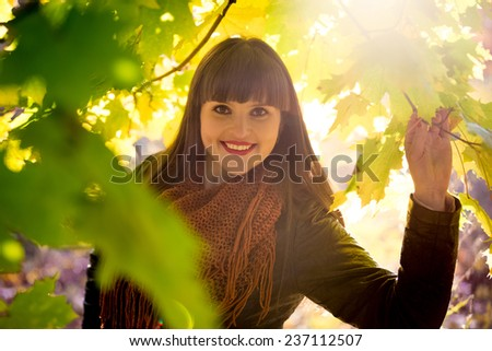 Closeup portrait of happy brunette woman standing under tree at autumn park - stock photo