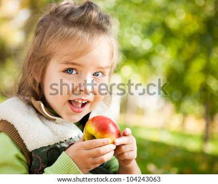 Closeup portrait of happy child eating red apple outdoors in autumn - stock photo