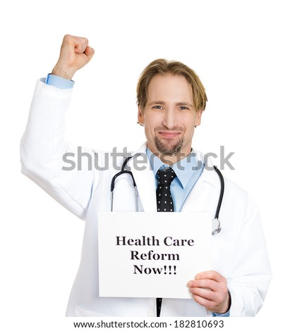 Closeup portrait of happy confident young doctor man with fist raised, holding health care reform now! sign, isolated white background. Government, federal politics, congress, insurance policy debate - stock photo