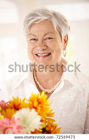 Closeup portrait of happy elderly woman holding flowers looking at camera, smiling.? - stock photo