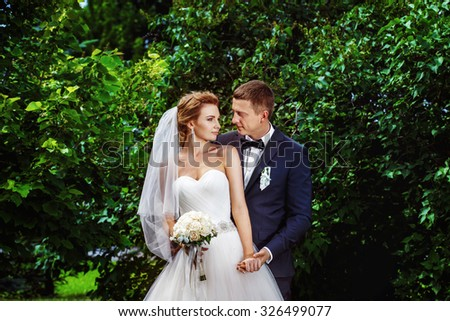 Closeup portrait of happy elegant groom embracing beautiful bride with wedding bouquet isolated at green bright summer park background. - stock photo