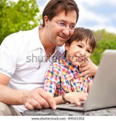 Closeup portrait of happy family: father and his son using laptop outdoor at their backyard sitting on the bench - stock photo