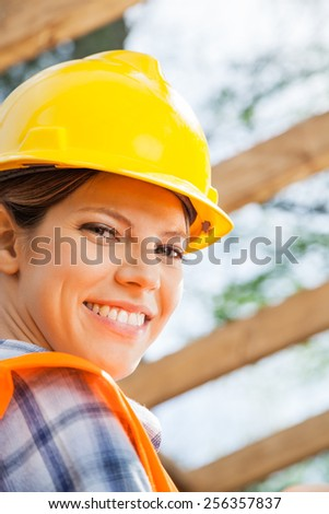 Closeup portrait of happy female construction worker at site - stock photo