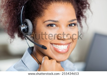 Closeup portrait of happy female customer service representative wearing headset in office - stock photo