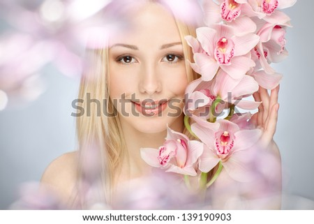 closeup portrait of happy girl with pink orchids over gray background - stock photo