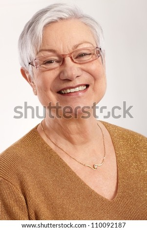 Closeup portrait of happy granny smiling in glasses and elegant sweater. - stock photo