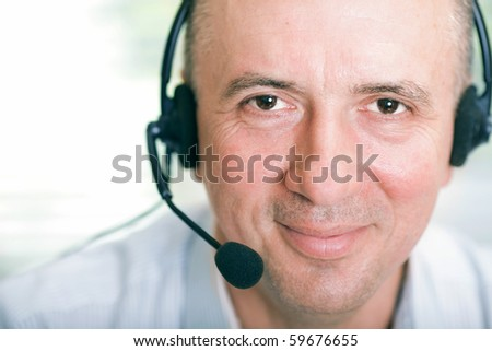 Closeup portrait of happy mature business man with headset - stock photo