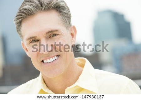 Closeup portrait of happy mature man with buildings in background - stock photo