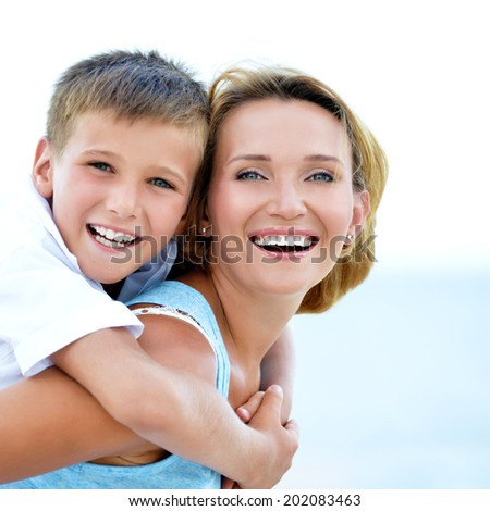 Closeup portrait of happy mother and son in embrace on the beach. - stock photo