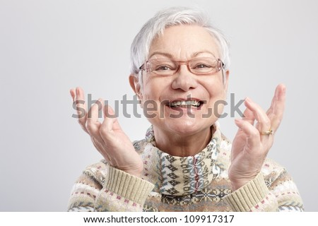 Closeup portrait of happy old woman gesturing by hands. - stock photo