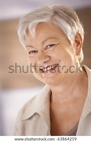 Closeup portrait of happy senior woman with white hair, looking at camera, smiling.? - stock photo