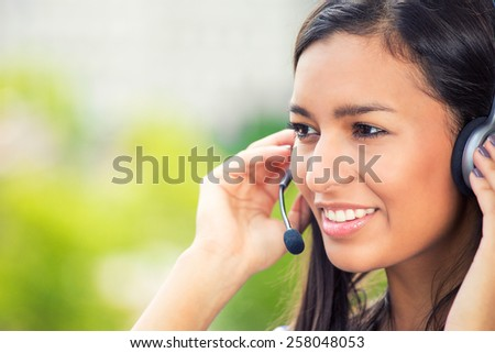 Closeup portrait of happy smiling cheerful support phone operator in headset at office - stock photo
