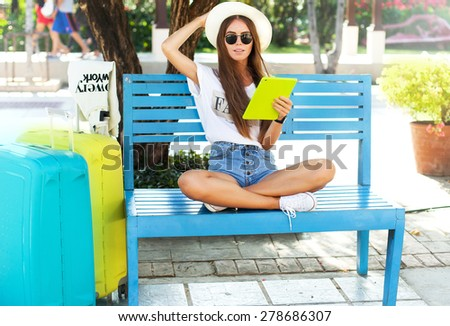 closeup portrait of happy woman in glasses using tablet pc in the airport wear summer clothes.Relaxing after long trip.beautiful young woman in heat sitting in park and holding tablet and smiling - stock photo
